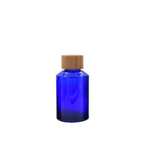 cosmetic blue glass bottle with bamboo cap